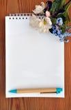 Leerseite eines Notizbuches und des Blumenstraußes der Vergissmeinnichte Lizenzfreies Stockbild
