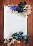 Leerseite eines Notizbuches und des Blumenstraußes der Vergissmeinnichte Stockfotografie