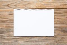 Leerseite eines Sketchbook auf einem alten Holztisch Lizenzfreie Stockfotos