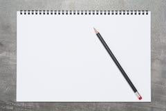 Leerseite eines Sketchbook mit einem schwarzen Bleistift auf einer grauen Oberfläche lizenzfreie stockfotografie