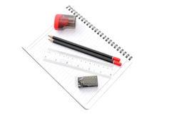 Leerseite mit Bleistiften, Radiergummi, Machthaber und Bleistiftspitzer Lizenzfreie Stockfotos