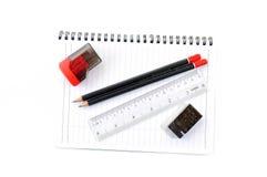 Leerseite mit Bleistiften, Radiergummi, Machthaber und Bleistiftspitzer Lizenzfreie Stockbilder