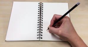 Leerseiten des offenen Buches mit der asiatischen männlichen Hand, die schwarzen Bleistift bereit, zu notieren hält Stockfotos