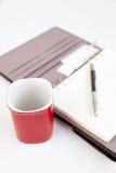 Leerseitentagebuchbleistift und roter Tasse Kaffee Stockbild
