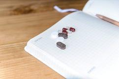 Leerstelle f?r Ihren Text auf einem Blatt des Notizbuches oder des Tagebuchs Medizinischer Hintergrund mit farbigen Tabletten, Ta lizenzfreies stockbild