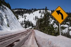 Left Curve Sign. Motorists are warned of a sharp turn ahead on a snowy mountain road in Montana stock images