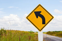 Left curved road traffic sign with windmill background and clear Royalty Free Stock Photos