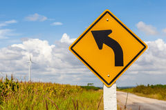 Left curved warning sign with windmill background in wind farm, Royalty Free Stock Image