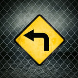 Left Direction Grunge Yellow Warning Sign on Chainlink Fence Stock Images