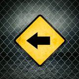 Left Direction Grunge Yellow Warning Sign on Chainlink Fence Royalty Free Stock Photography