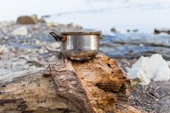 Left dirty pot on the river bank.  Stock Photos