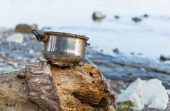 Left dirty pot on the river bank.  Stock Photo