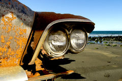 Left for good. Old decaying vintage car on the beach Stock Photos