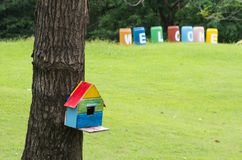 Colourful birdhouse in the green garden stock image