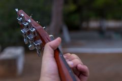 Hand and fretboard. Left hand close up playing a chord on a guitar fretboard outside at a park royalty free stock images