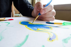 Left hand draws brush with blue paint on paper in album with sev Stock Photos