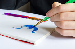 Left hand draws brush with blue paint on paper in album with sev Royalty Free Stock Photography