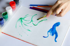 Left hand draws brush with green paint on paper in album with se Stock Photos