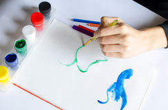 Left hand draws brush with green paint on paper in album with se Royalty Free Stock Photography