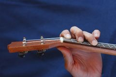 Left musician hand clamps the chord on the ukulele, top view Stock Photo
