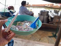 Left hand holding a bowl of noodles. The river is behind and there are noodle boats. thailand lifestyle Royalty Free Stock Photos