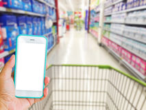 Left hand holding green mobile phone with supermarket blur backg Royalty Free Stock Photo