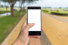 Left hand holds mobile phone with black white background Royalty Free Stock Image