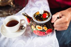 Left hand holds a teapot royalty free stock photography