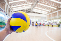 Left hand holds a volleyball Stock Images