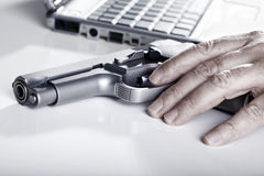 Computer Criminal. The left hand of a mature adult man resting on a 9mm handgun, and a defocused laptop computer in the background. Backlit Royalty Free Stock Photography