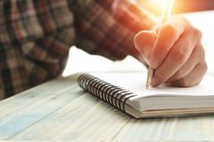 Left hand of people, student writing and note on notebook on wood table with copy space, in library, concept as education attempt. And make effort to win Stock Image