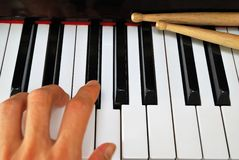Left hand playing on piano keyboard Stock Image