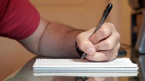 Left hand writing math on a note pad. Closeup of a left hand writing math on a note pad stock video footage