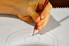 Left handed artist with an unusual pencil grip. Pencil sketch in the haida style, created by drawing geometrical concentric shapes. Haida is an artform developed stock image