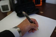 Signing documents and paperworks. Left handed businessman signing documents and paperworks, cropped image. Selective focus Stock Photography