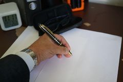 Signing documents and paperworks. Left handed businessman signing documents and paperworks, cropped image. Selective focus Royalty Free Stock Images