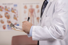 A left handed doctor writes on a patients chart. Royalty Free Stock Photos