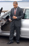 Left Handed Ethnic Business Man Using PDA. Left handed ethnic business man using a PDA next to his luxury car parked at the lake. He is wearing a suit and tie royalty free stock images