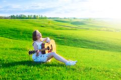 Left-handed irl playing guitar outdoor on green spring grass meadow royalty free stock photos