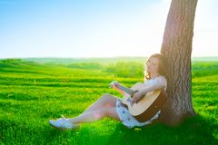 Left-handed irl playing guitar outdoor on green spring grass meadow royalty free stock photography