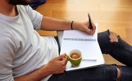 Left handed man writing, sitting on the floor. Royalty Free Stock Images
