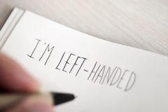 Left-handed man writing the text I am left-handed Stock Photo
