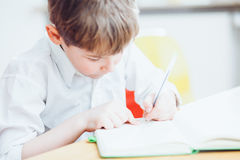 Left handed school boy writing or drawing in book Stock Photo