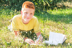 Left-handed teen lying and reading on the grass. Stock Photos