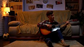 Left-handed teenage student playing guitar at home relaxing after lectures hobby. Stock photo royalty free stock images