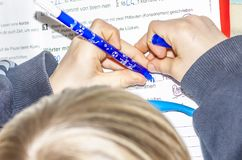 Left handed young doing his homework - Translation: read short time too pause sleeping burningif two consonants written royalty free stock photos
