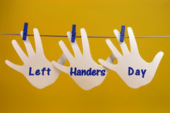Left Handers Day message greeting across left hand silhouette cards hanging from pegs on a line. Against a yellow background, for International Left-handers Day royalty free stock photos
