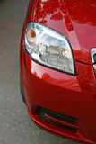 The left headlight. Of the new red car Stock Photo