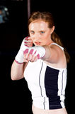 Left Jab. Beautiful but dangerous young woman fighter throws a stiff left jab while training in an MMA gym stock photography