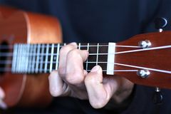 Left musician hand clamps the chord on the ukulele fretboard Stock Photo